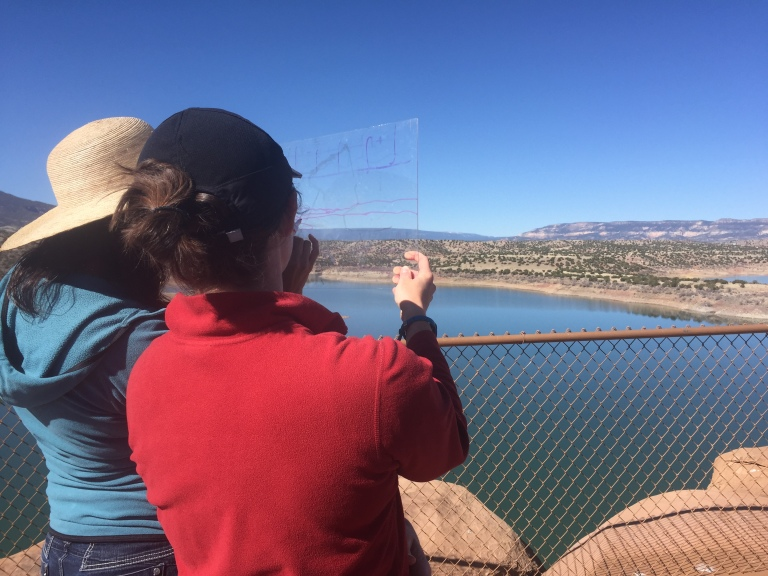 Two teachers practice drawing landforms on plexiglass.