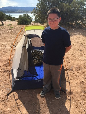 A camper stands beside his tent.